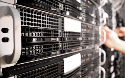 Photo of several racked servers and out of focus hand installing one