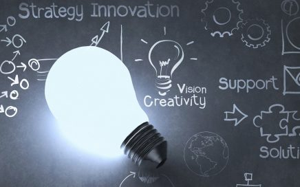 Photo of an illuminated light bulb against a blackboard with words in chalk saying strategy innovation vision creativity solution
